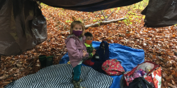 children playing in the woods in a crafted tent