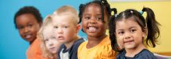 Five diverse children smiling at camera
