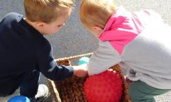 Two children look through a basket of balls.