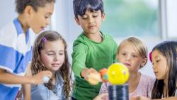 A small group of children conducts an experiment