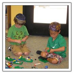 Two boys playing with blocks on floor