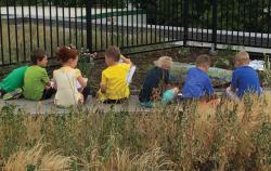 Row of children sitting outside near a garden