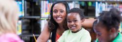 Ealr childhood educator assisting students with writing