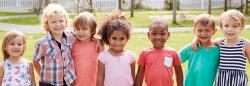 A diverse group of preschool-aged children posing together outside