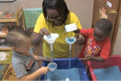 Teacher and children play with funnels at sand table.