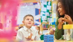 A young boy practices counting with his teacher.