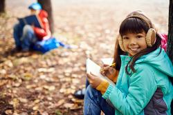 A young girl draws and takes notes in a forest