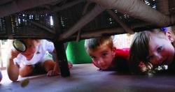 Children searching with magnifying glass under furniture.