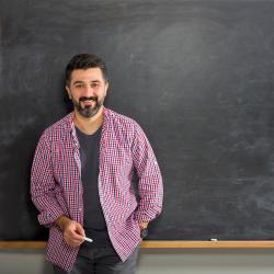 Man in front of chalk board