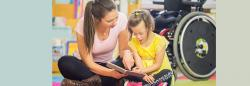 Teacher and student in wheelchair reading together