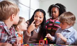 Teacher and preschool age students sitting at table with materials