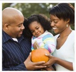 father, mother, and daughter holding a pumpkin