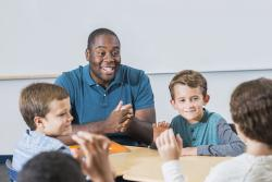 Young black male teacher of color sites at a table with group of white boys.