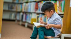 Preschool boy reading a book in the library