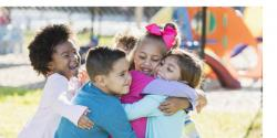 A group of diverse young children hugging on a playground