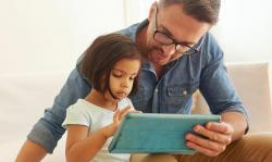 father and daughter looking at computer tablet