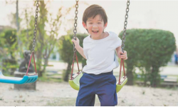 Boy smiles has he plays on the swing