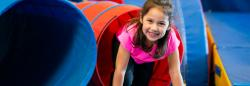 Young girl climbing out of a slide.
