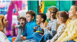 Six children laughing and talking to teacher
