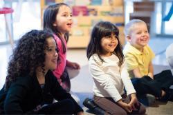 Four preschool students sitting on floor