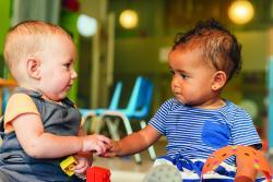 Infants holding hands