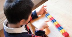 Boy counting his lego blocks