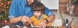 Father and son painting wooden materials