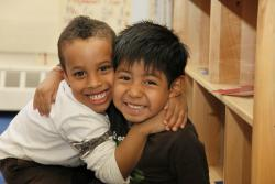 Two young boys of color embrace and small into the camera.