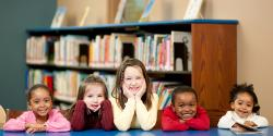 Five young children sitting at a table in the library