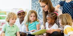 Teacher in a classroom reading to five children