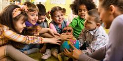 Diverse group of preschoolers with their hands on a globe