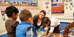 A teacher observing young children who are exploring a map in a classroom.
