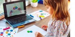 Una niña haciendo arte frente a una computadora.