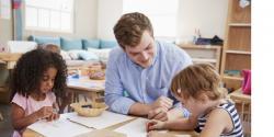 A teacher instructing young children in a classroom.