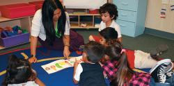 Preschool teacher showing students a picture book
