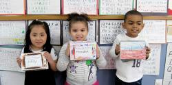 Three students holding their math mini-books