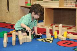 Preschool boy playing with blocks and a toy car on the floor