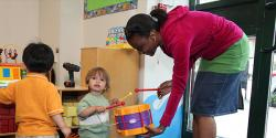 Teacher plays with a young child using a drum