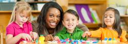 Preschool teacher helping three students build with blocks
