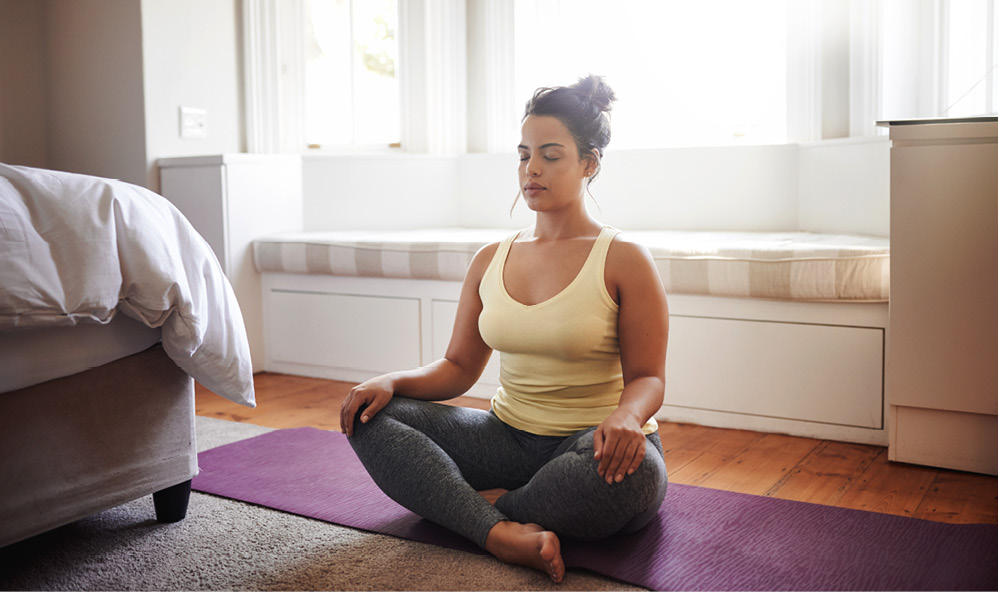woman doing yoga sitting cross-legged on the floor of a bedroom