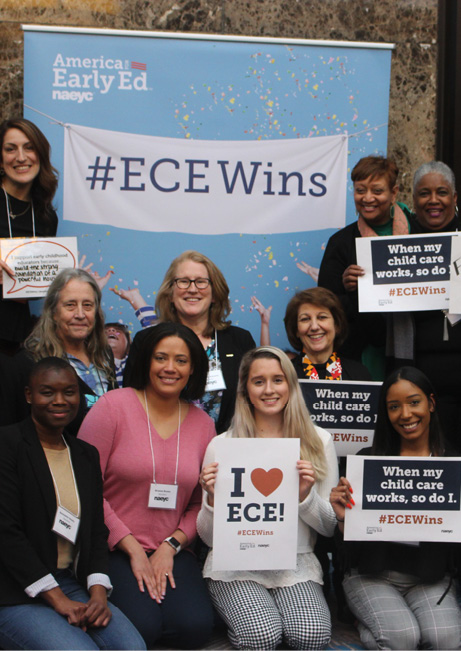 photo of NAEYC members in front of the America for Early Ed poster holding up signs in support of ECE